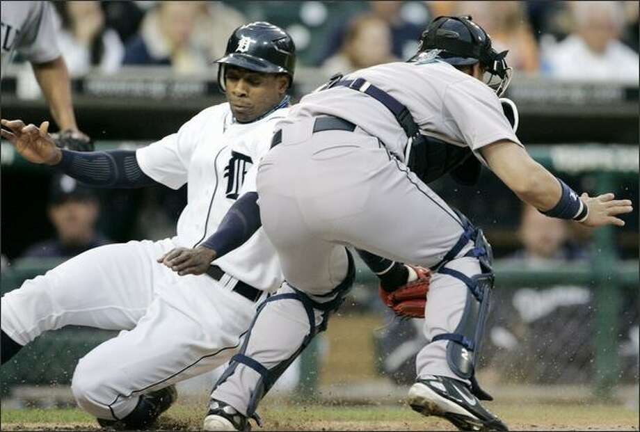 Detroit's Curtis Granderson slides past Mariners catcher Kenji Johjima in the fifth inning. Granderson scored from second base on a single by Placido Polanco. Photo: Associated Press / Associated Press
