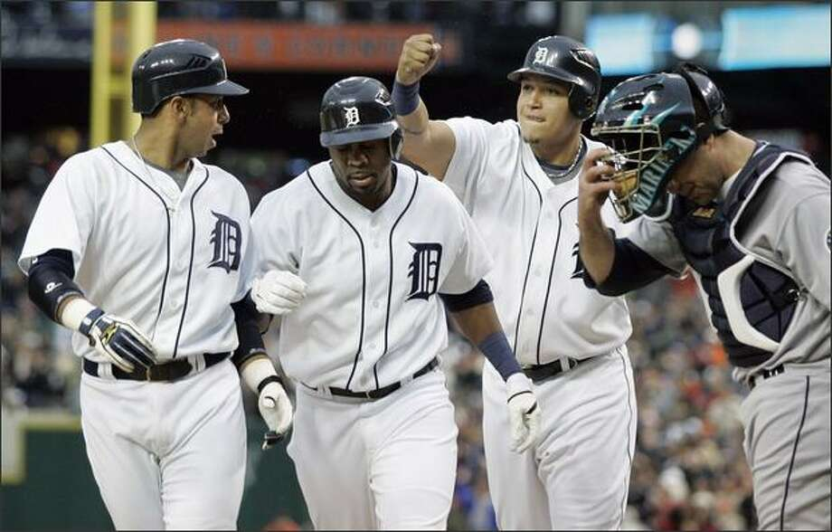 From left, Carlos Guillen, Marcus Thames and Miguel Cabrera celebrate Thames' grand slam as they pass Mariners catcher Jamie Burke, right, in the third inning. Detroit's Magglio Ordonez also scored. Photo: Associated Press / Associated Press