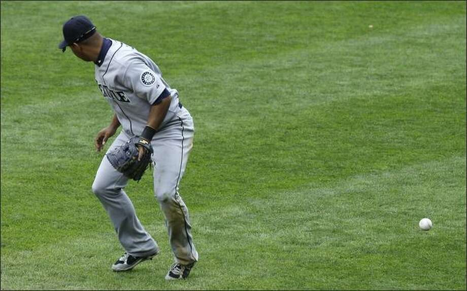 Mariners second baseman Jose Lopez lets a ground ball hit by Derek Jeter slip by for an error in the sixth inning. Jeter then scored on a home run by Bobby Abreu. Photo: Associated Press / Associated Press