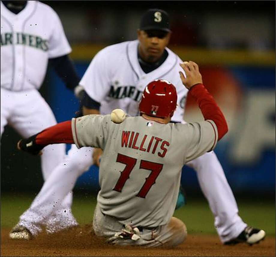 Angels' Reggie Willits beats the throw in the first inning as he slides to second base. The ball hit him in the back after Richie Sexson's throw was too low to complete the double play off the bat of Maicer Izturis as the Seattle Mariners play the Los Angeles Angels at Safeco Field. Photo: Scott Eklund, Seattle Post-Intelligencer / Seattle Post-Intelligencer