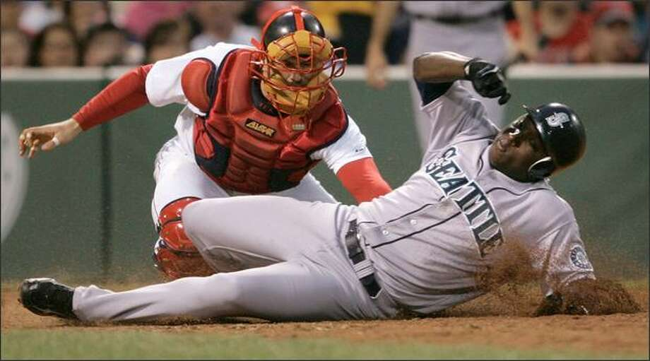 Yuniesky Betancourt slides as he beats the tag by Red Sox catcher Jason Varitek to score on a single by Ichiro Suzuki in the fourth inning. Photo: Associated Press / Associated Press