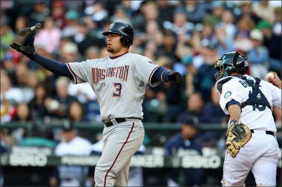 Washington's Jesus Flores, left, catches his bat after ending the third inning by striking out as Mariners catcher Jamie Burke heads to the dugout. Photo: Associated Press / Associated Press