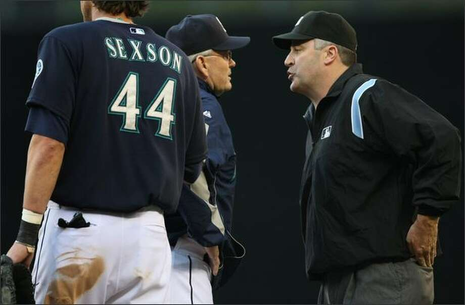 Seattle Mariners manager John McLaren argues what appeared to be a double-play at first base with umpire Bill Welke who called Florida Marlins Jeremy Hermida safe at first. Photo: Joshua Trujillo, Seattlepi.com / seattlepi.com