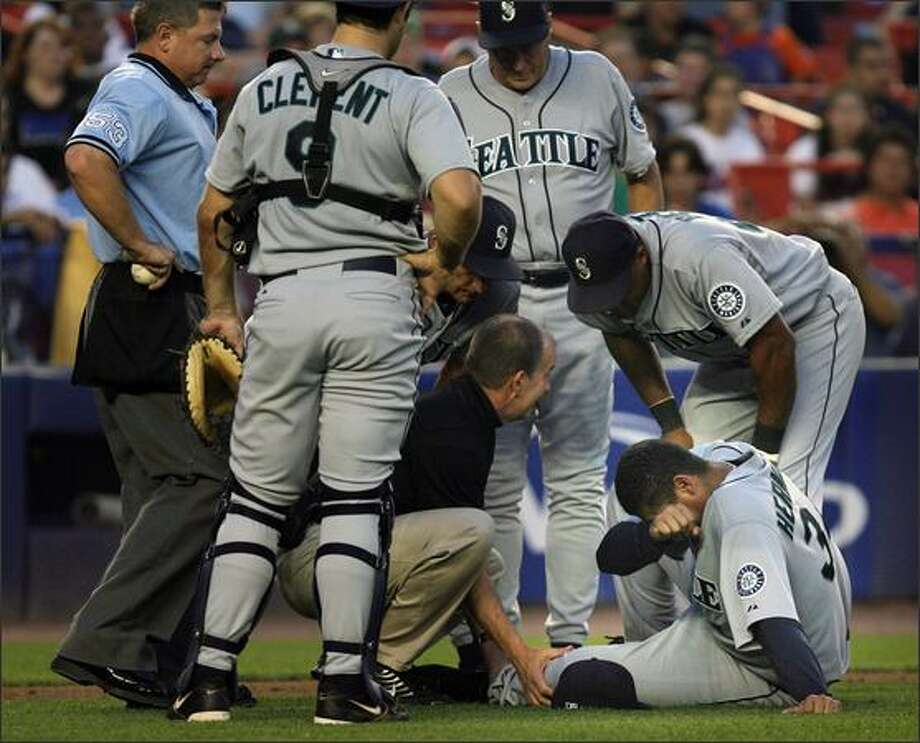Seattle Mariners' Felix Hernandez, on the ground,  hides his head in his arm after being hit when the New York Mets' Carlos Beltran slid into home plate during the fifth inning. Hernandez left the game. Photo: Associated Press / Associated Press