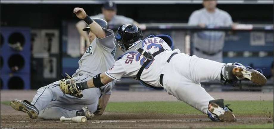 Willie Bloomquist, left, avoids the tag from Mets catcher Brian Schneider as he slides home to score during the second inning at Shea Stadium in New York. Bloomquist and Kenji Johjima were able to score on a fielding error by Mets second baseman Luis Castillo on a ball hit by Jose Lopez. Photo: Associated Press / Associated Press