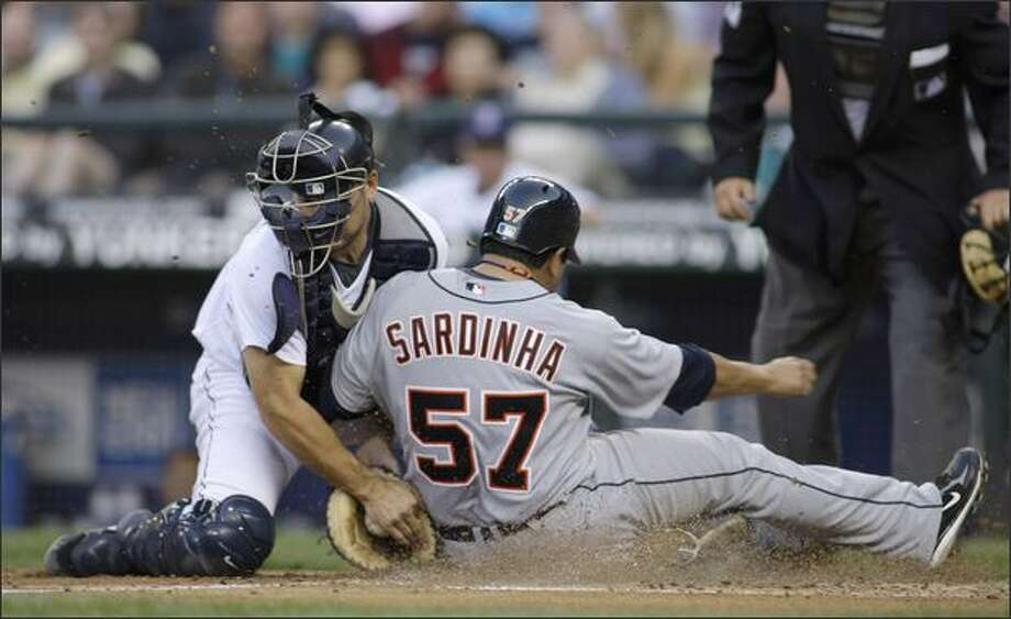 Detroit's Dane Sardinha is tagged out at home plate by Mariners catcher Jeff Clement after Sardinha tried to score on a single hit by Placido Polanco in the fifth inning. Photo: Associated Press / Associated Press