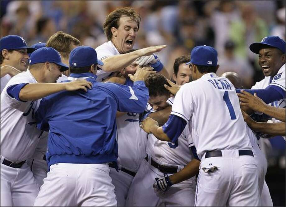 David DeJesus, center, is swarmed by teammates after hitting a two-run home run in the ninth inning to beat the Mariners 5-4. Photo: Associated Press / Associated Press