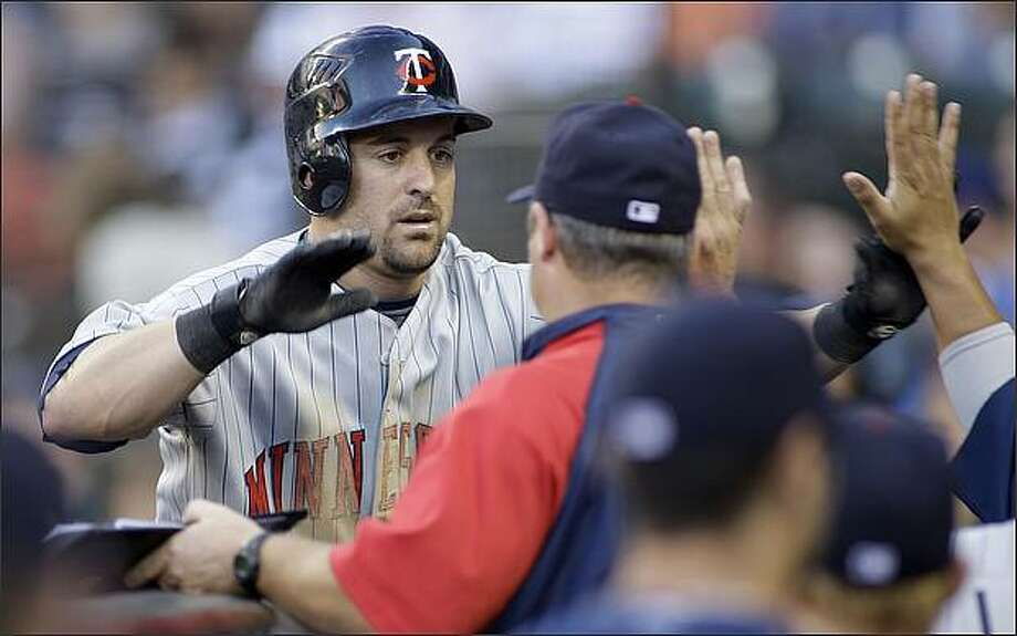 Minnesota Twins' Nick Punto is greeted at the dugout after he hit a solo home run against the Seattle Mariners in the third inning. (AP Photo/Ted S. Warren)