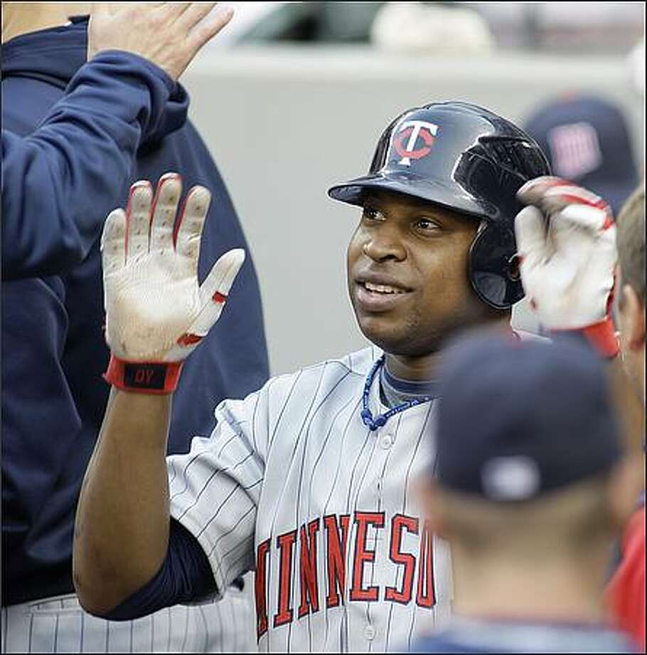 Minnesota Twins' Delmon Young is greeted in the dugout after he scored in the second inning on a sacrifice fly by Brendan Harris against the Seattle Mariners. (AP Photo/Ted S. Warren)