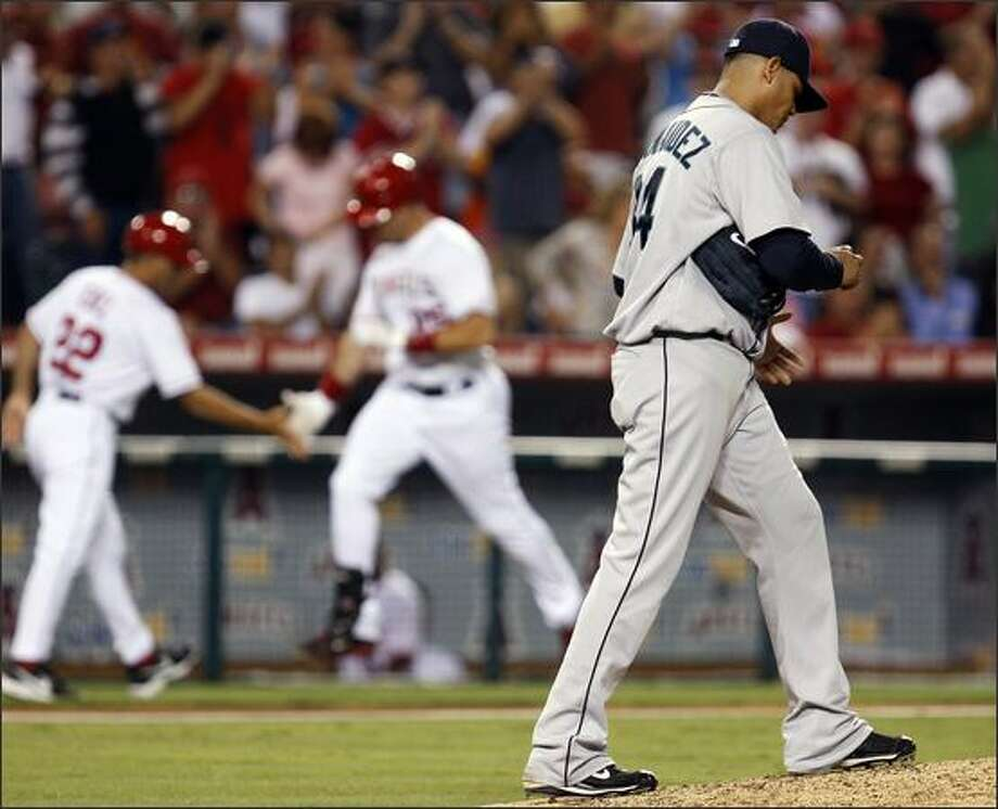 Seattle Mariners pitcher Felix Hernandez, right, walks back to the mound after giving up a two-run home run to the Los Angeles Angels' Mark Teixeira, center, during the third inning of a baseball game in Anaheim, Calif., Wednesday, Aug. 13, 2008. (AP Photo/Matt Sayles) Photo: Associated Press / Associated Press