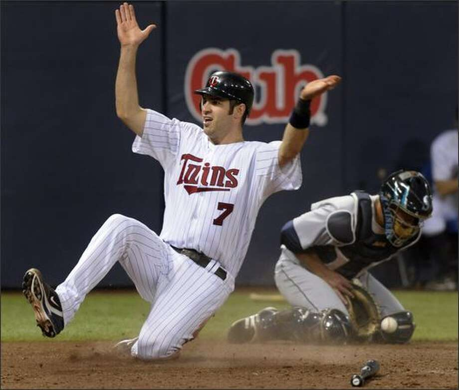 Minnesota Twins' Joe Mauer (7) slides across homeplate with the winning run as Seattle Mariners catcher Jamie Burke, right, fields the throw during the ninth inning in an MLB baseball game, Saturday, Aug. 16, 2008 in Minneapolis. Minnesota won 7-6. (AP Photo/Tom Olmscheid) Photo: Associated Press / Associated Press