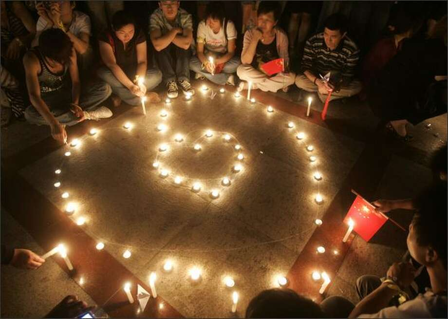 People attend a candlelight vigil to pray for the survivors and the victims of an earthquake at the Renmin Square in Shanghai, China on May 21. The Sichuan government vowed to build houses for 98 percent of the earthquake refugees within a month. A major earthquake measuring 8.0 on the Richter scale, the worst in 58 years, jolted China's Sichuan Province May 12. Photo: Getty Images / Getty Images