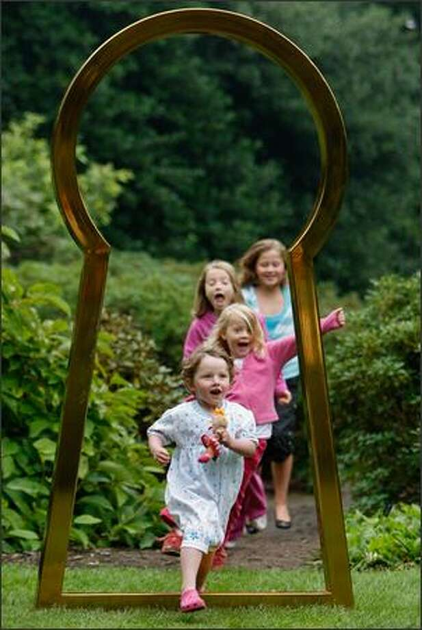 Children jump through an 8-foot-tall keyhole, one of seven on display at the Royal Botanic Garden in Edinburgh, Scotland. The artwork created by Turner-prize nominated Jim Lambie is being premiered at the Edinburgh Arts Festival and is expected to be one of the highlights. Photo: Getty Images / Getty Images