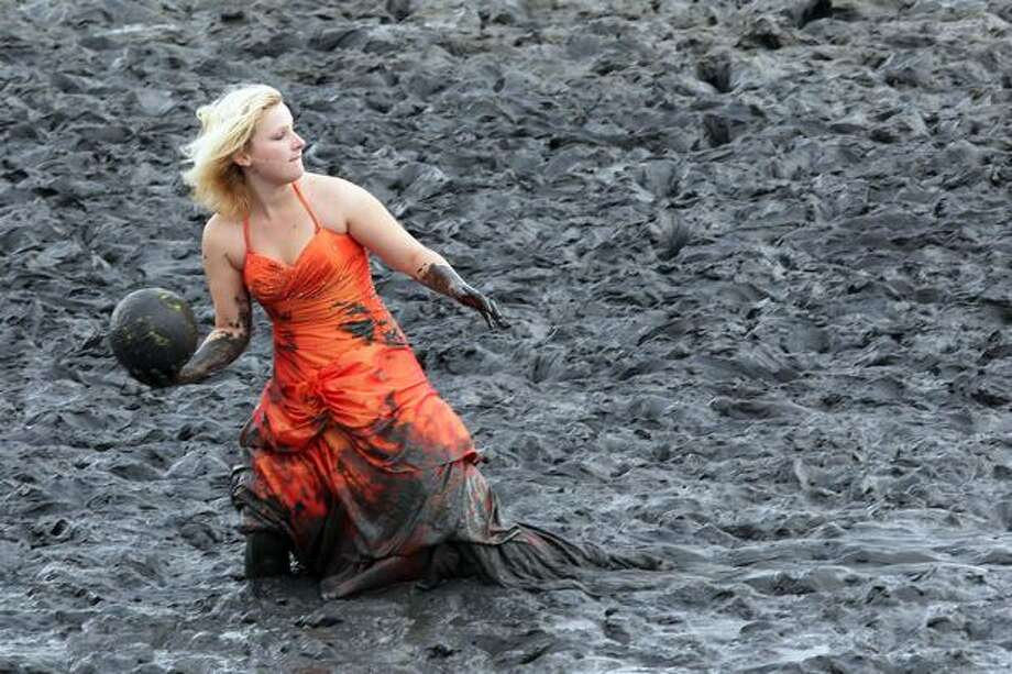 A participant of the fashion show throws a ball during the Mudflat Olympic Games in Brunsbuttel, Germany. Photo: Getty Images / Getty Images