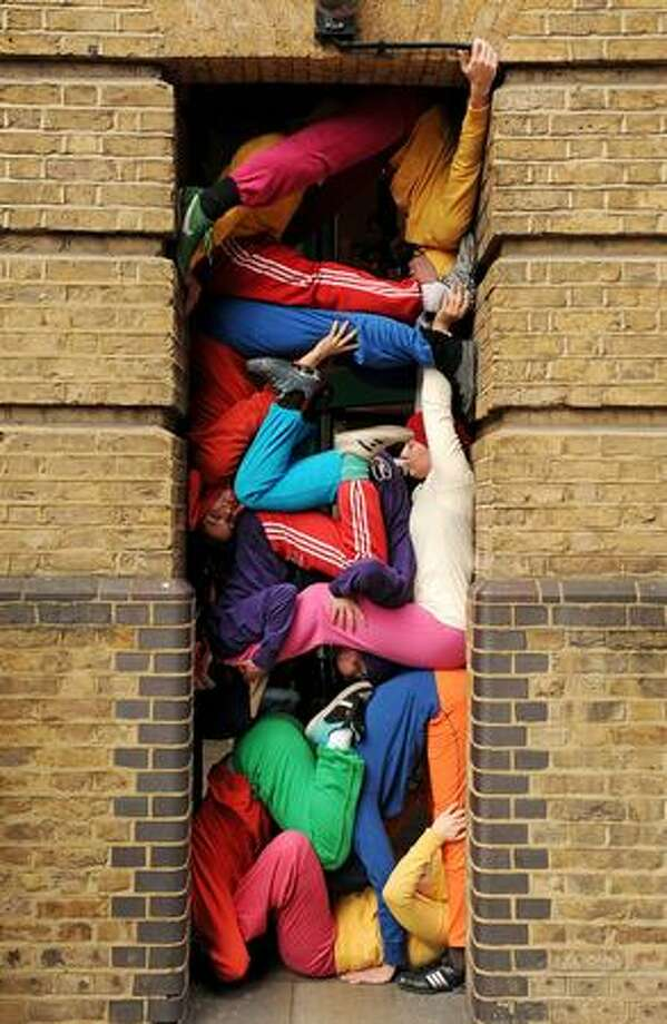 "Members of Austrian artist Willi Dorner's ""Bodies in Spaces"" performing arts troupe assume positions in urban spaces in London. Over 20 performers wearing brightly colored tracksuits formed human sculptures in awkward spaces and positions over a period of an hour along a route toured by members of the public. Photo: Getty Images / Getty Images"