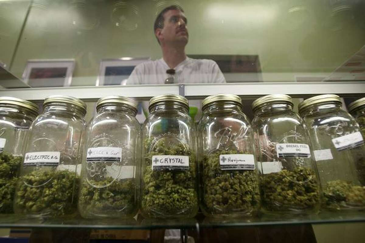 Dave Warden, a bud tender at Private Organic Therapy (P.O.T.), a non-profit co-operative medical marijuana dispensary, displays various types of marijuana available to patients in Los Angeles, California.