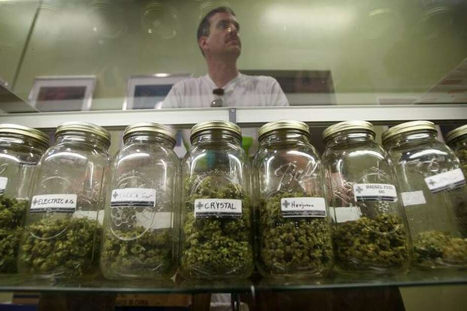Dave Warden, a bud tender at Private Organic Therapy (P.O.T.), a non-profit co-operative medical marijuana dispensary, displays various types of marijuana available to patients in Los Angeles, California. Photo: Getty Images / Getty Images