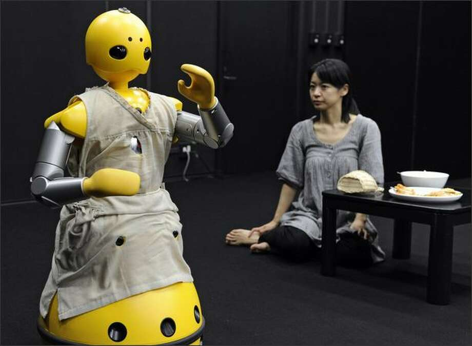 A humanoid robot, produced by Japan's Mitsubishi Heavy Industry, named Momoko, and actress Minako Inoue take part in a drama for the world's first robot and human experimental theatre, written and directed by Japanese playwright Oriza Hirata, at Japan's Osaka University in Osaka, Japan. The 20-minute performance was put on display for the media ahead of a possible run for the public next year. Photo: Getty Images / Getty Images