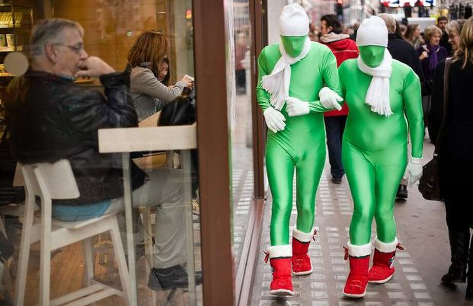 Street performers walk among shoppers on Oxford Street, in central London. Photo: Getty Images / Getty Images