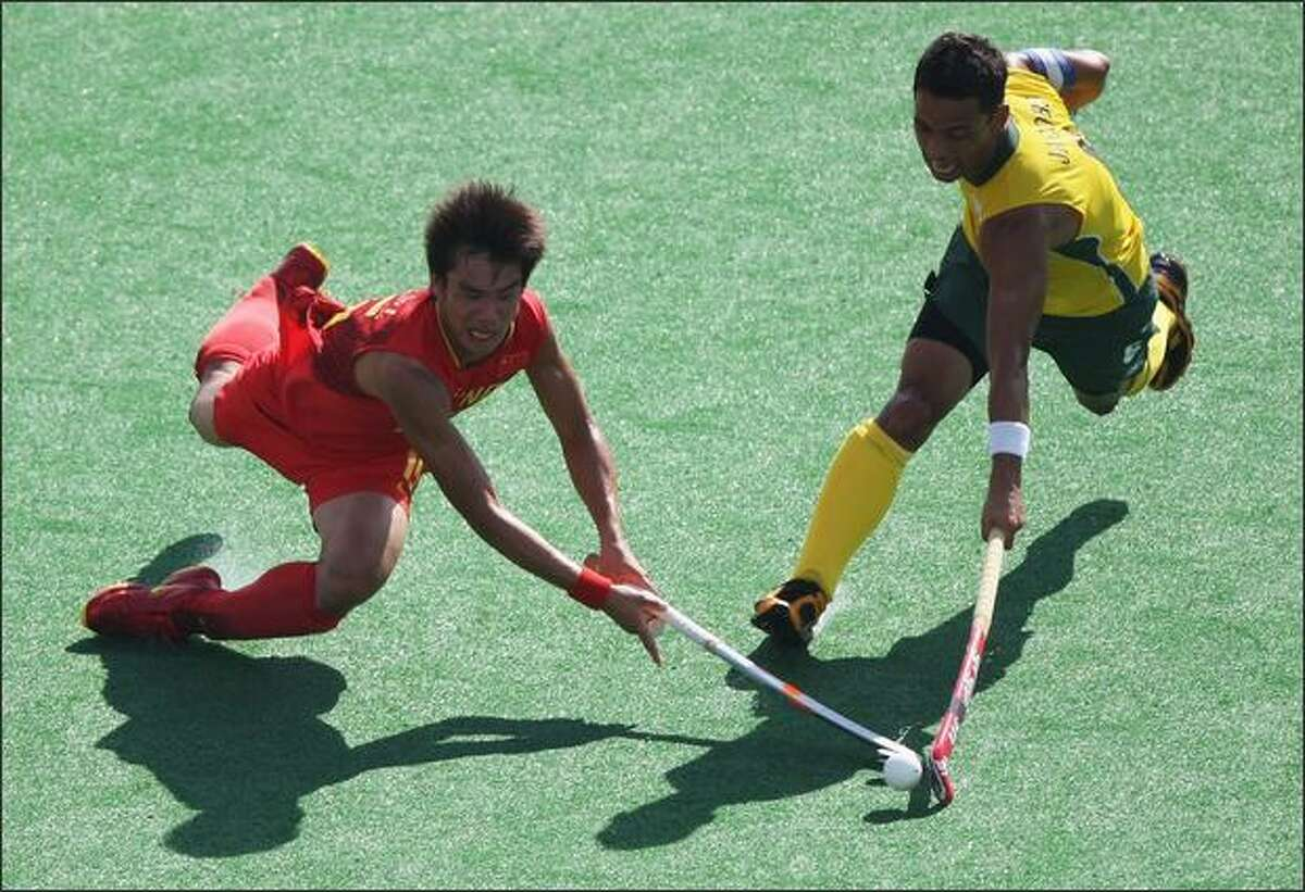 BEIJING - AUGUST 23: Meng Lizhi #16 of China and Bruce Jacobs #6 of South Africa compete in the Men's Classification 11-12 match between China and South Africa held at the Olympic Green Hockey Field on Day 15 of the Beijing 2008 Olympic Games on August 23, 2008 in Beijing, China.