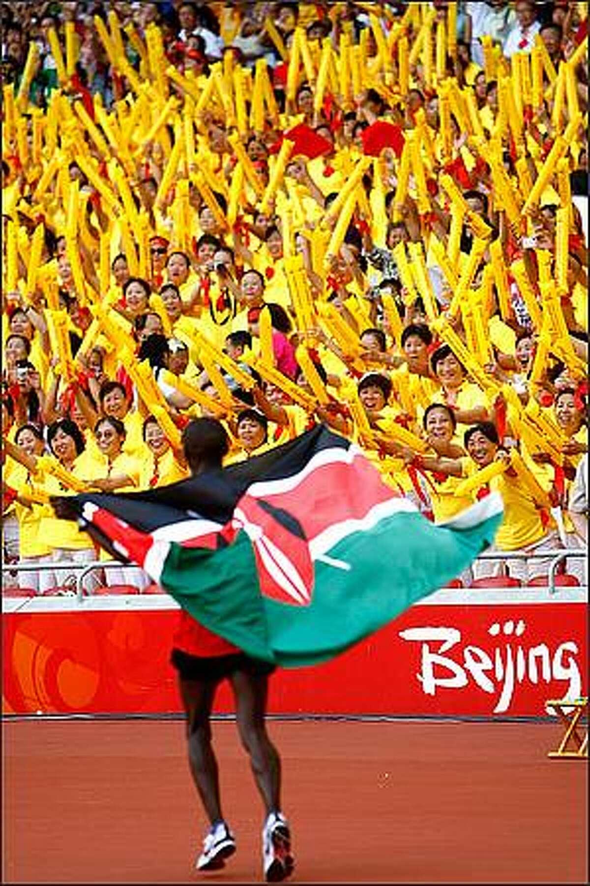 Samuel Kamau Wansiru of Kenya celebrates after winning the Men's Marathon in the National Stadium during Day 16 of the Beijing 2008 Olympic Games on Sunday in Beijing.