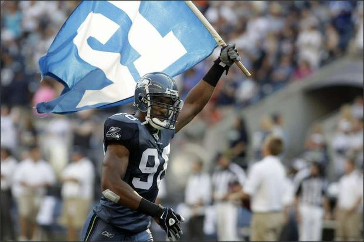 Julian Peterson carries the 12th Man flag into Qwest Field during the player introductions.