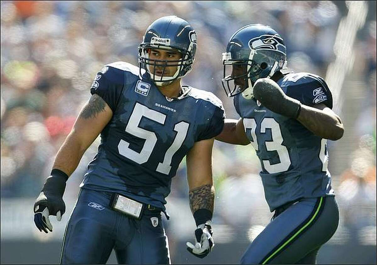 Seattle Seahawks linebacker Lofa Tatupu and cornerback Marcus Trufant, both sporting casts on their hands, confer during their game against the San Francisco 49ers.