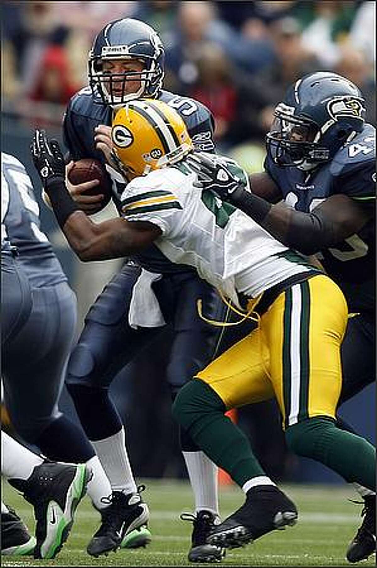 Seattle Seahawks quarterback Charlie Frye is sacked for a loss of five yards by Green Bay Packers cornerback Charles Woodson during the first quarter.