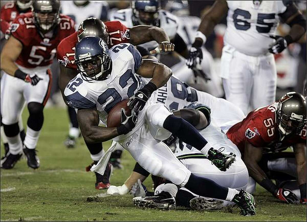 Seattle Seahawks running back Julius Jones runs for a short gain as he is tackled by Tampa Bay Buccaneers defensive end Jovan Haye (71) after being tripped up by Derrick Brooks (55) during the first half.