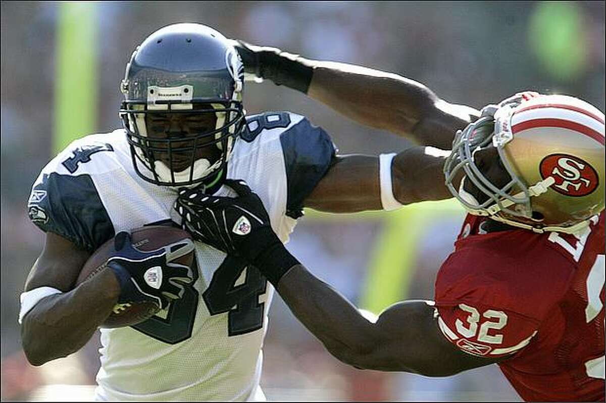 Seattle Seahawks wide receiver Bobby Engram, left, tries to avoid the tackle of San Francisco 49ers safety Michael Lewis in the first quarter. (AP Photo/Ben Margot)