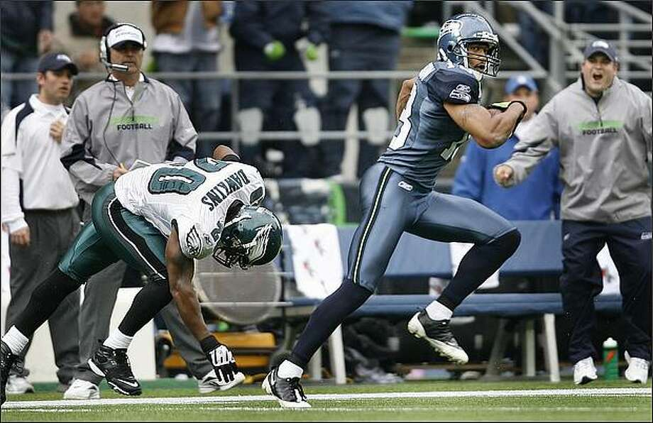 Seahawks wide receiver Koren Robinson eludes Philadelphia Eagles safety Brian Dawkins for a 90-yard touchdown reception in the first quarter at Qwest Field Sunday. The touchdown was the only score for the Seahawks in their 26-7 loss. Photo: Dan DeLong, Seattle Post-Intelligencer / Seattle Post-Intelligencer