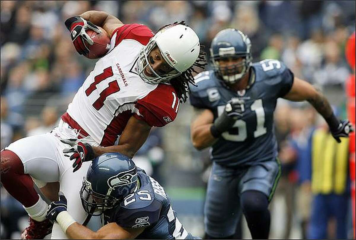 Arizona Cardinals wide receiver Larry Fitzgerald is brought down by Seattle Seahawks safety Brian Russell after a twenty-yard gain during first quarter action.