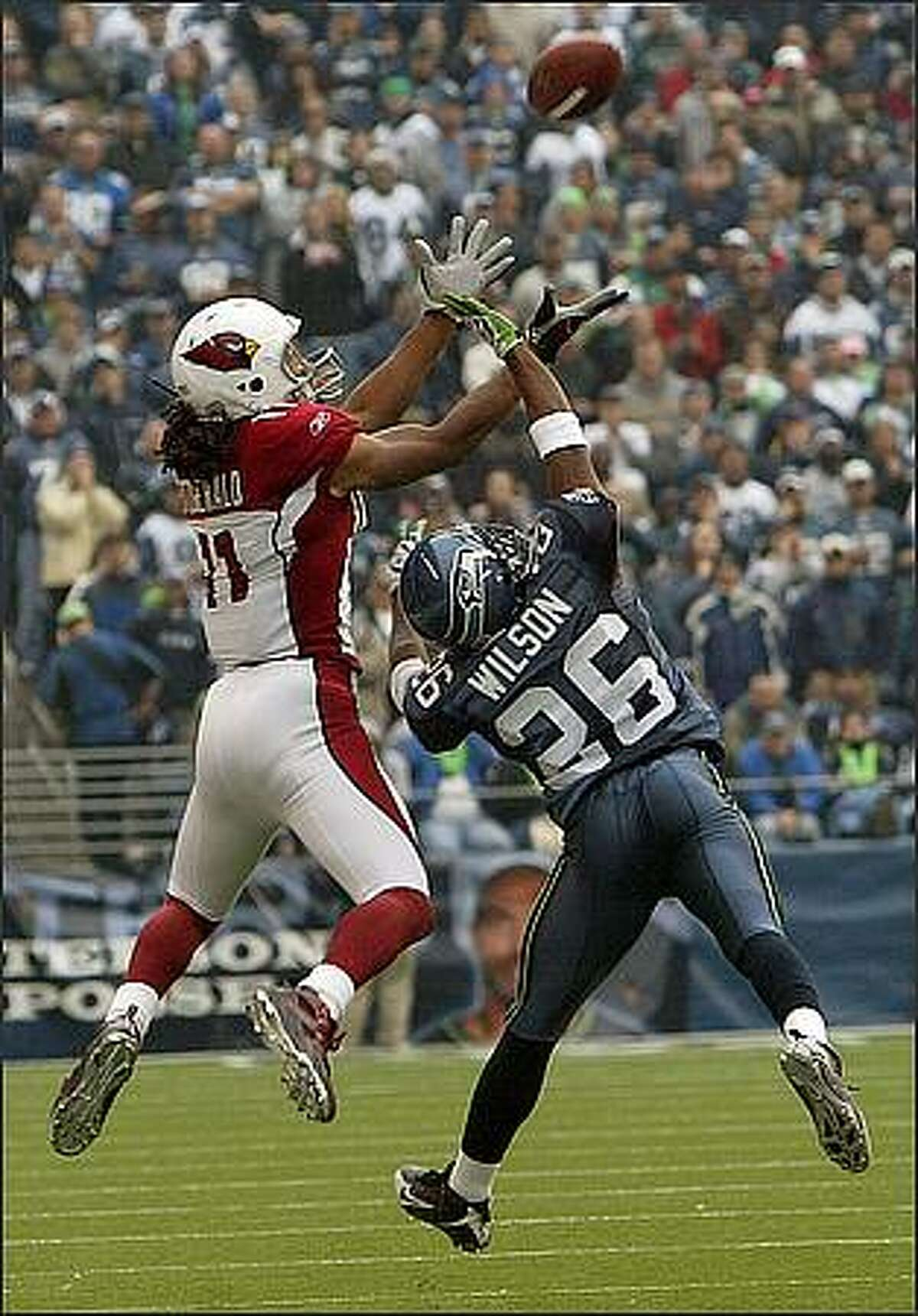 Seattle Seahawks cornerback Josh Wilson tries to defend against Arizona Cardinals wide receiver Larry Fitzgerald as he hauls in a 15-yard pass from Kurt Warner during second quarter action.