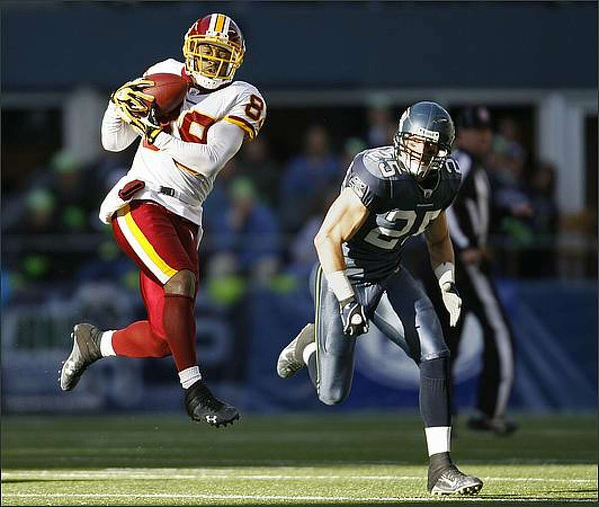 Washington Redskins wide receiver Santana Moss pulls in a 20-yard catch before being tackled by Seattle Seahawks safety Brian Russell in the 1st quarter.