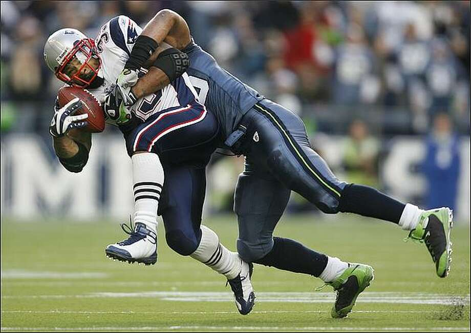 Seattle Seahawks linebacker Julian Peterson tackles New England Patriots running back Kevin Faulk for a four-yard loss in the 1st quarter. Photo: Dan DeLong, Seattle Post-Intelligencer / Seattle Post-Intelligencer