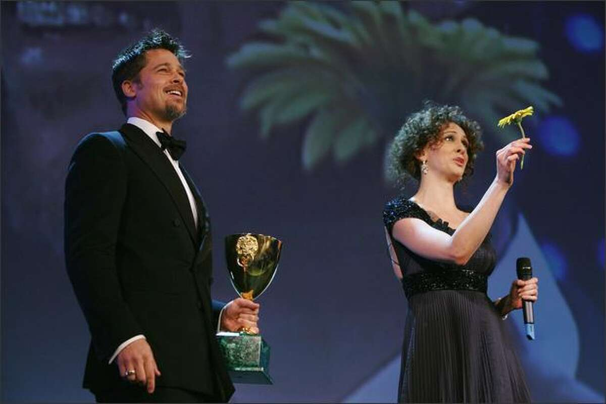 Actor Brad Pitt and host actress Ksenia Rappoport pose with the 2007 Coppa Volpi for Best Actor for the movie