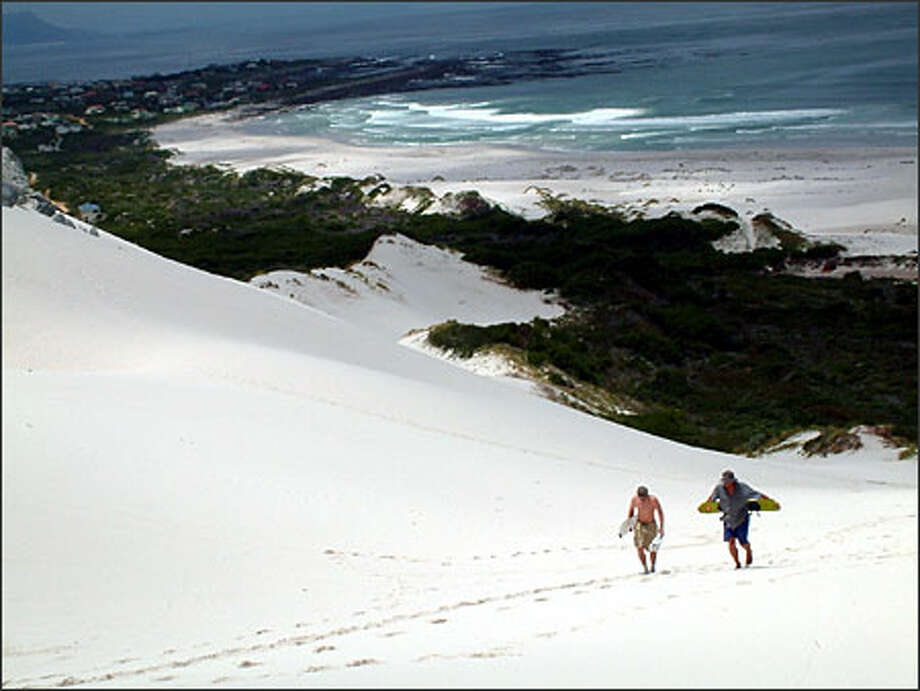 Sandboarding instructor Gordon Neethling and traveling Seattleite Richie Costleigh climb a hill overlooking Betty's Bay in South Africa. Sandboarding in South Africa (unlike snowboarding in North America) doesn't come with that wonderful invention: the chair lift. Photo: Winda Benedetti, Special To Seattle Post-Intelligencer / Special to Seattle Post-Intelligencer