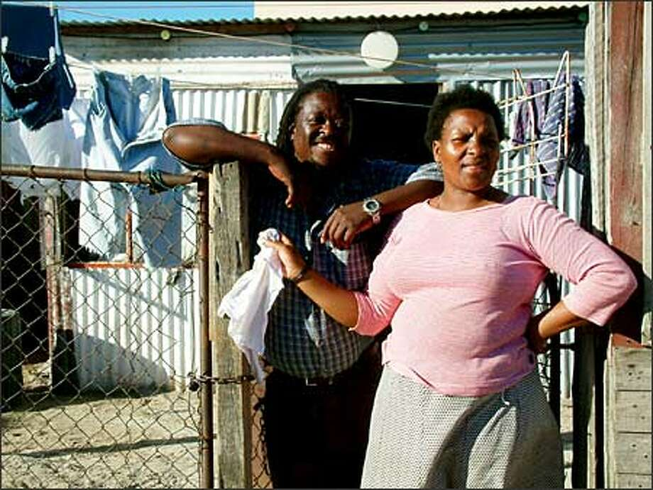 Joyce Nkope and her husband Petros stand in front of their home in the township of Crossroads. During apartheid, the government tried to eradicate villages like these. People were dragged from their homes, which were then bulldozed over. Many were killed in the process. Crossroads became a center of black resistance to apartheid. Photo: Winda Benedetti, Special To Seattle Post-Intelligencer / Special to Seattle Post-Intelligencer