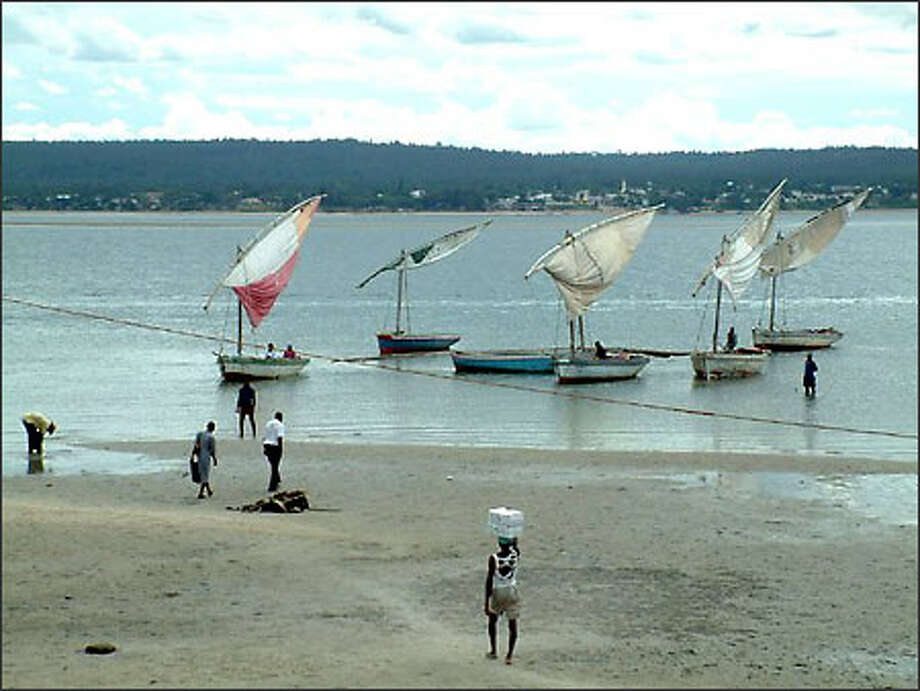 Traditional wooden sailboats called dhows wait to ferry passengers from the town of Inhambane to Maxixe in Mozambique. In the 1700s the Portuguese opened a trading post in Inhambane through which slaves and Ivory were frequently exported. Today many of the old buildings still stand. Photo: Winda Benedetti, Special To Seattle Post-Intelligencer / Special to Seattle Post-Intelligencer