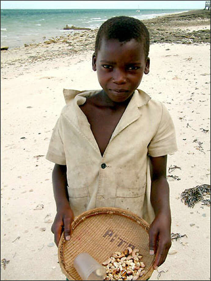 A young boy sells cashews in the town of Vilankulo. In Mozambique, which still rates among the world's poorest countries, children often work to help their families earn money and raise money so they can go to school. Cashews are one of the country's primary crops. Photo: Winda Benedetti, Special To Seattle Post-Intelligencer / Special to Seattle Post-Intelligencer