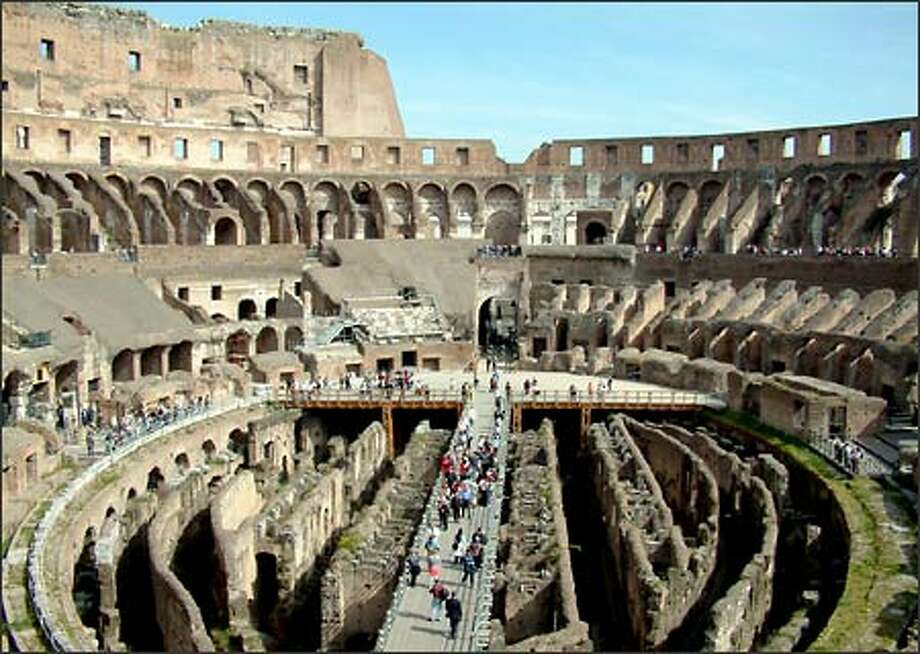 Although tourism across Europe was down this spring due to the war in Iraq, travelers continued to visit many of the world's most famous attractions. Here, small crowds take a gander at Rome's Colosseum. Dedicated by Emporer Titus in 80 A.D., the Colosseum today stands as a monument to many things - history, architecture and man's thirst for both entertainment and blood. Photo: Winda Benedetti, Special To Seattle Post-Intelligencer / Special to Seattle Post-Intelligencer
