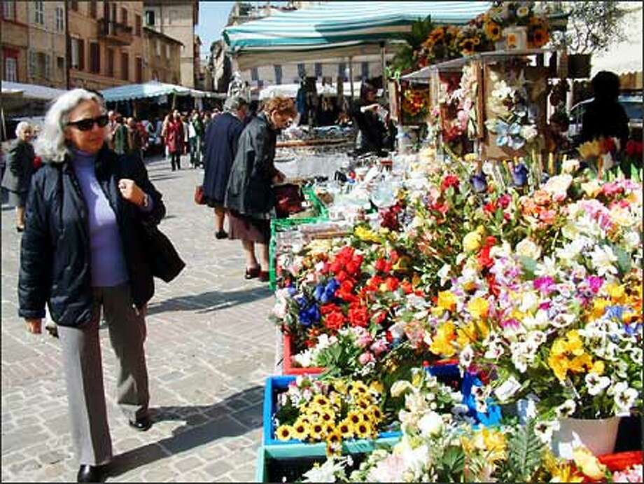 Shoppers peruse the flowers, clothes and other goods on sale at the open air market in Macerata. This small town in northeastern Italy is the place from where my family originally comes. Photo: Winda Benedetti, Special To Seattle Post-Intelligencer / Special to Seattle Post-Intelligencer