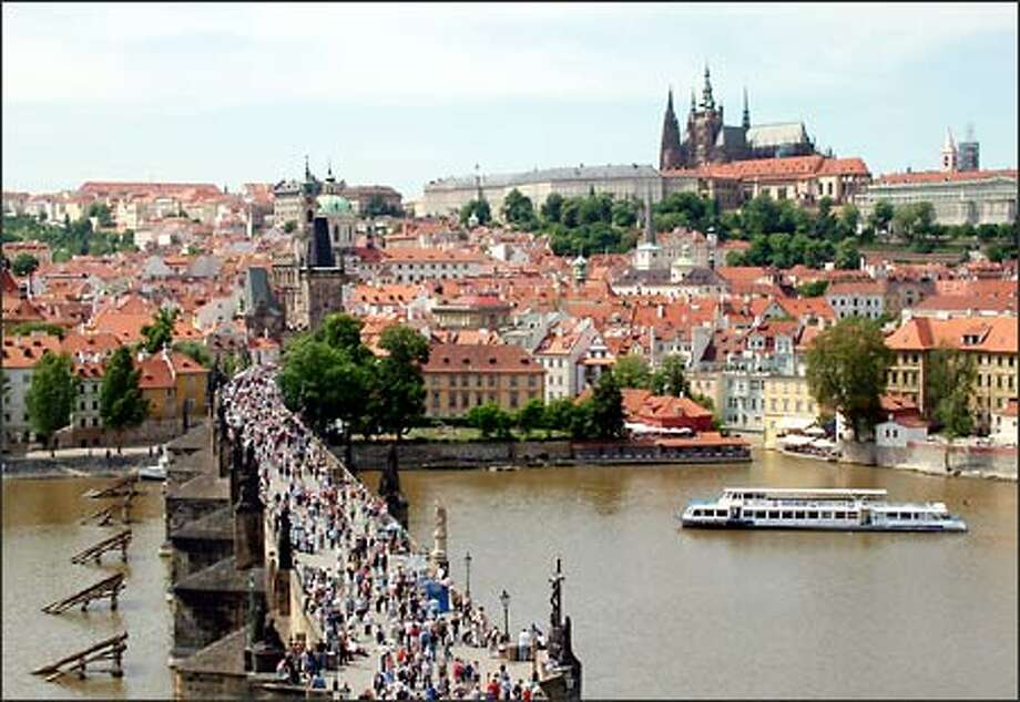 Prague is such a remarkably beautiful city today because it remained nearly unscathed during WWII. The saint-statued Charles Bridge spans the Vltava River and was commissioned by Holy Roman Emperor Charles IV in the 14th Century. As you can probably tell by the crowds, this bridge is one of Prague's main attractions. In the distance you can see another: The castle district of Hradcany, home to Prague Castle and St. Vitus Cathedral. The imposing gothic cathedral got underway way back in 1344 but wasn't finished until 1929. Photo: Winda Benedetti, Special To Seattle Post-Intelligencer / Special to Seattle Post-Intelligencer