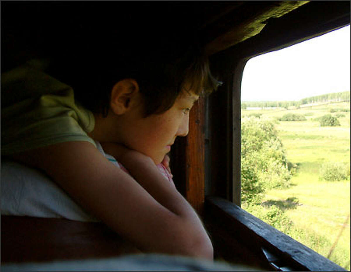 Yura, a 13-year-old Russian from the town of Yekaterinburg, watches the Siberian landscape pass the window of our train compartment.