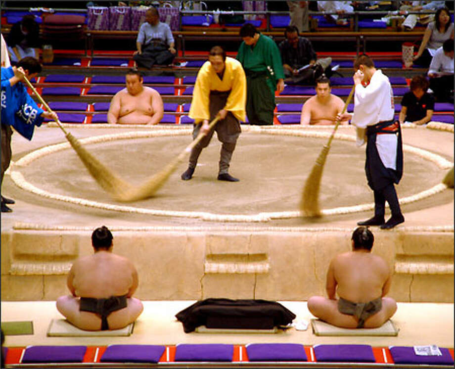 Sweepers prepare the dohyo (sumo ring) for the next round of competition as wrestlers patiently await their turn at battle. Sumo wrestling is the oldest martial art form in Japan, dating back more than 1500 years. There are six grand tournaments a year, each one lasting 15 days. Richie and I were lucky enough to attend the final day of the final tournament of the season at Aichi Prefectural Gymnasium in Nagoya. Photo: Winda Benedetti, Special To Seattle Post-Intelligencer / Special to Seattle Post-Intelligencer