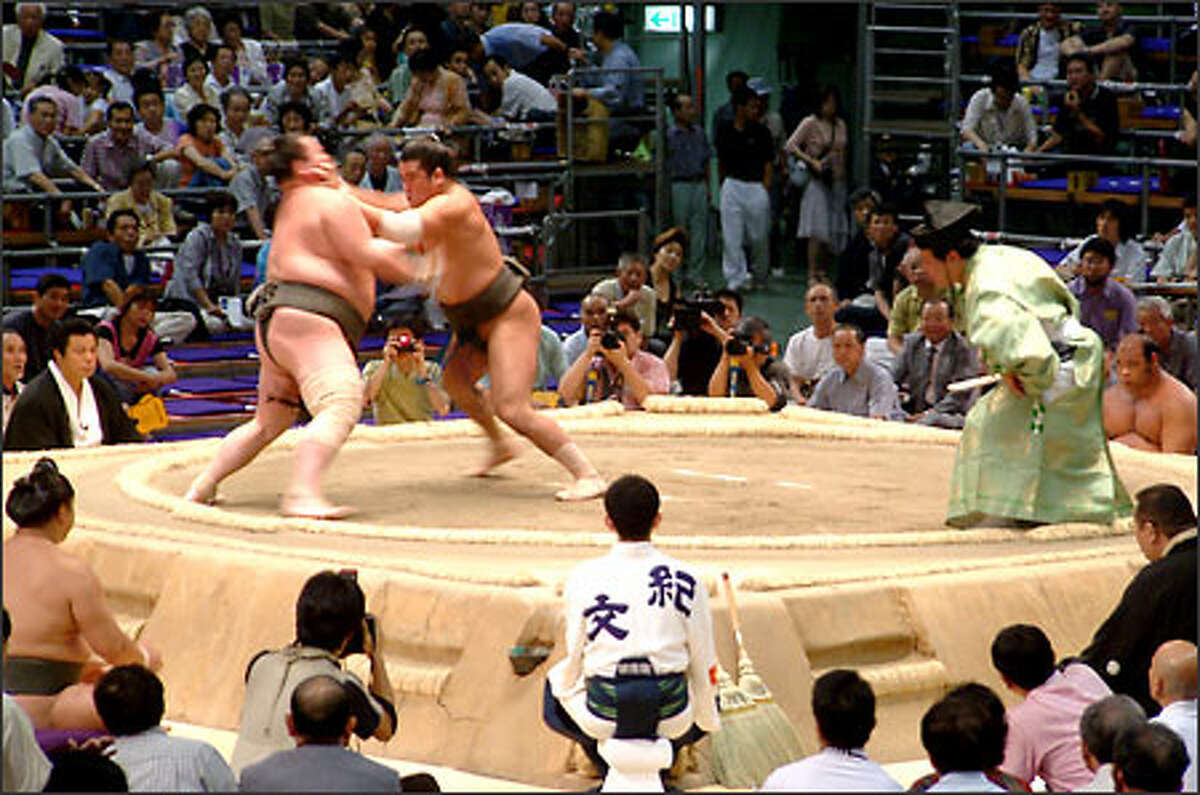 A gyoji (referee) watches while two wrestlers clash. Sumo matches are fast and fierce. These massive men slap, shove, pull and throw each other, each one attempting to force the other out of the ring or to the ground.