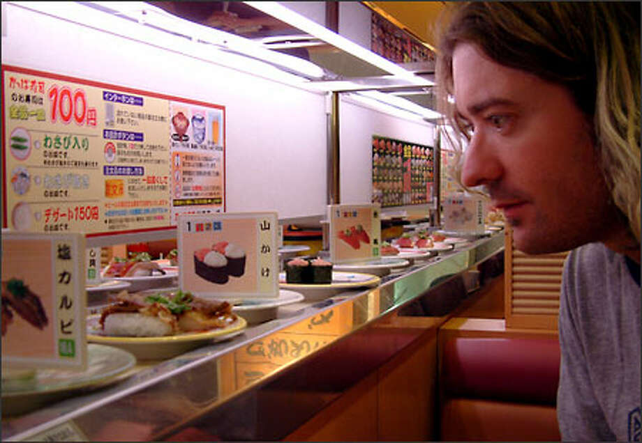 Richie fishes for dinner at one of Kyoto's many conveyor-belt sushi joints. Japan was a terrifyingly expensive place for a couple of budget travelers like us to spend time. We bled money on a daily basis. Sushi, however, was one of the few bargains we found. Restaurants that specialized in delivering raw fish to diners on conveyor belts usually offered plates of salmon, tuna, eel, etc. for between $1.50 and $2 each. Photo: Winda Benedetti, Special To Seattle Post-Intelligencer / Special to Seattle Post-Intelligencer
