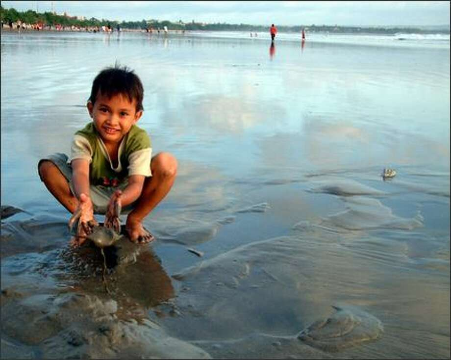 A boy plays in the sand at Kuta beach on the Indonesian island of Bali. Kuta is the busiest beach on the island, popular with surfers, swimmers and soccer players and not-so-popular among those who want to get away from it all. Photo: Winda Benedetti, Special To Seattle Post-Intelligencer / Special to Seattle Post-Intelligencer