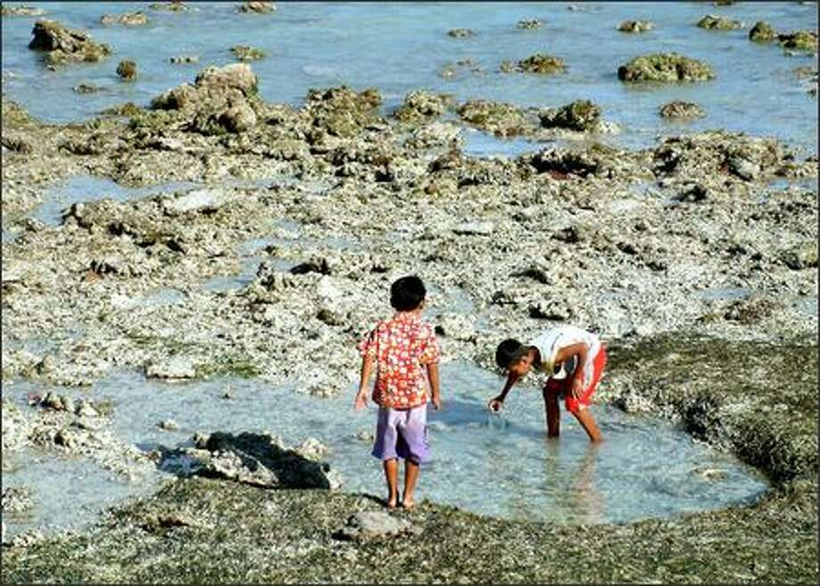 Boys play in the tide pools along Gili Trawangan's east coast. Trawangan is one of three small islands clustered near the larger Indonesian island of Lombok. No motorized vehicles are allowed on this little slice of paradise. Transportation is by foot, bicycle or horse-drawn cart only. Photo: Winda Benedetti, Special To Seattle Post-Intelligencer / Special to Seattle Post-Intelligencer