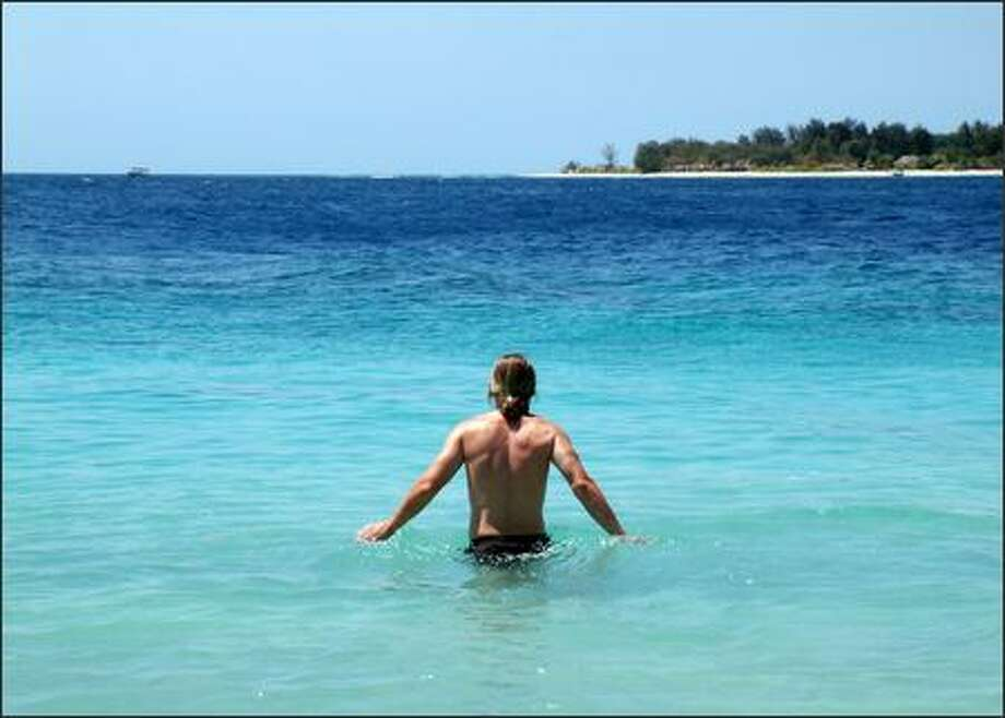 Richie wades into the ultra-blue H20 off the shore of Gili Trawangan. Photo: Winda Benedetti, Special To Seattle Post-Intelligencer / Special to Seattle Post-Intelligencer